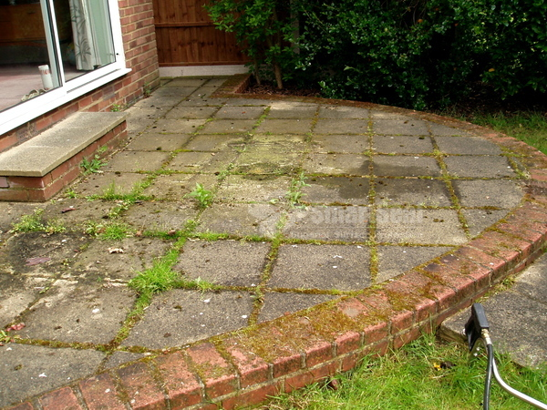 Patio slabs with significant dirt and weed growth